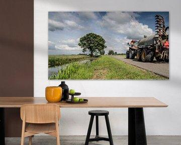 De boer aan het werk met zijn tractor van André Hamerpagt