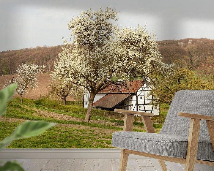 Sfeerimpressie behang: Vakwerkhuisje tussen de bloesem van John Kreukniet