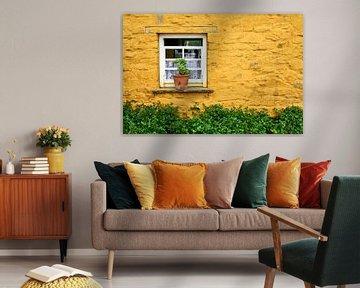 Venster in gele muur van een Ierse cottage