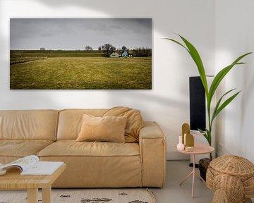 Landschap met dijk, dijkhuizen, grasland en dreigende lucht van Dirk Huckriede