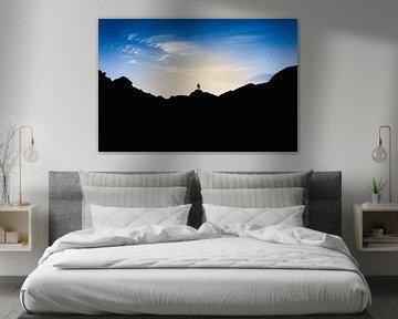 Silhouetten van twee mensen die op de top van een berg staan bij zonsondergang. Wout Kok One2expose van Wout Kok