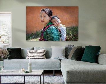 Jonge bhutanese vrouw mat baby op rug in Wangdi Bhutan. Wout Kok One2expose van Wout Kok