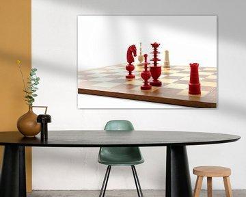 Rode en witte ivoren schaakstukken op een houten bord van Wim Stolwerk