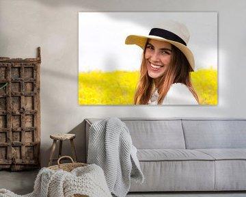 Porträt einer jungen Frau mit Strohhut vor einem gelben Blumenfeld von Anita Hermans