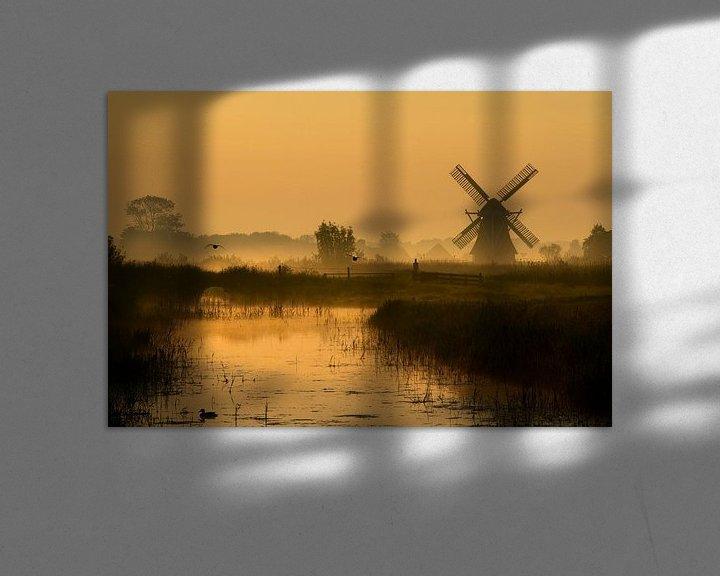 Sfeerimpressie: Nederlands poldermolen in het gouden licht van de vroege ochtend van Mark Scheper