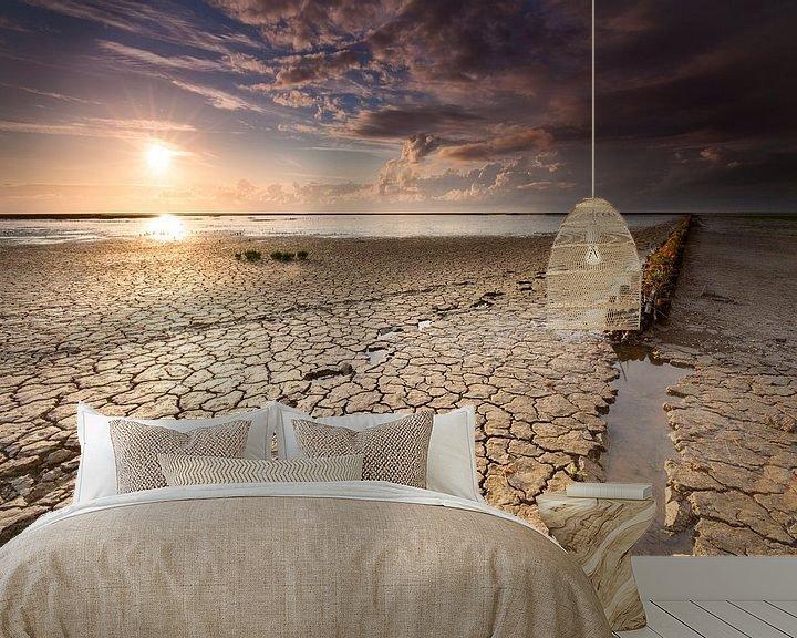 Sfeerimpressie behang: Voetstappen en strekdam in wadden modder bij zonsondergang.  van Mark Scheper