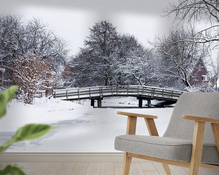 Sfeerimpressie behang: Houten fietsbrug in een besneeuwd landschap van Bert Meijerink