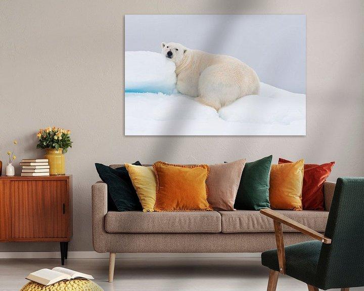 Sfeerimpressie: Rustende ijsbeer ligt op heuvel van sneeuw van Caroline Piek