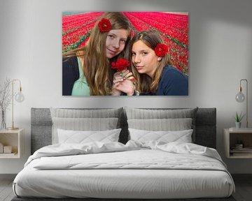 Zwei holländische Mädchen riechen rote Rosen bei Tulpenfeld von Ben Schonewille