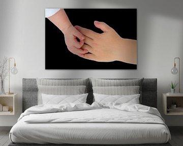 Hand von Neugeborenen in Kontakt mit der Hand eines Kindes von Ben Schonewille