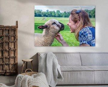 Porträt einer Frau die ein junges Schaf oder Lamm streicht sur Ben Schonewille