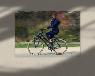 Een jonge vrouw fietst door het park in Amsterdam.  van Hamperium Photography