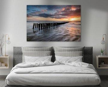 Paalhoofden op het strand tijdens zonsondergang van Arnoud van de Weerd