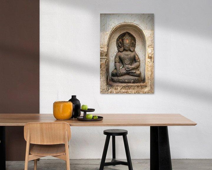 Impression: Statue de Bouddha dans une niche d'un mur blanc d'un temple au Népal sur Rietje Bulthuis