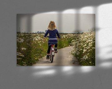 Meisje fietsend door een  bloemen zee von piet douma