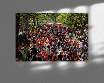 Oranje mensenmassa in het Vondelpark in Amsterdam op Koninginnedag van Merijn van der Vliet