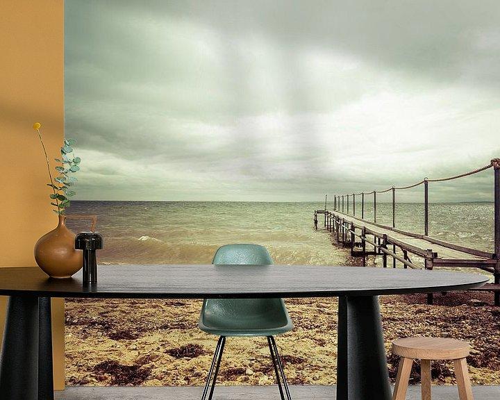 Sfeerimpressie behang: Steiger aan het strand bij een bewolkte lucht van Tony Buijse