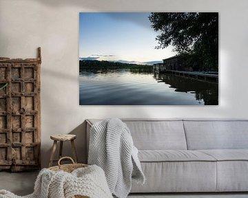 Landscape on a lake with boatshouse in the evening van Rico Ködder