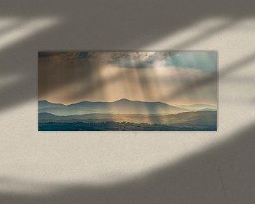 Lichtstralen over de heuvels in Toscane ... van Marc de IJk