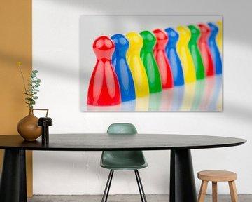 Conceptuele gekleurde speelpionnen in een rij von Tonko Oosterink