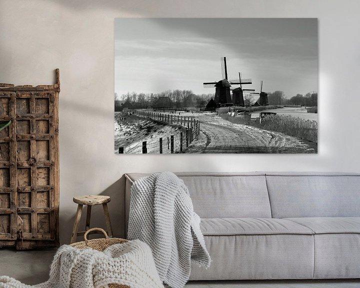 Sfeerimpressie: Hollandse molens langs vaart in winter van Paul Franke