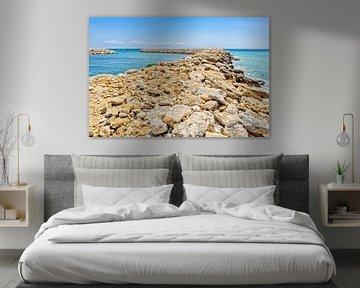 Rij rotsen en keien als pier in griekse zee van Ben Schonewille