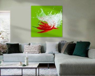 Contrastrijke foto van rode pepers vallend in het water van Henny Brouwers