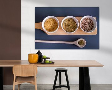 Houten plank met quinoa, rijst en couscous in witte schaaltjes - houten lepel met kruiden van Malu de Jong