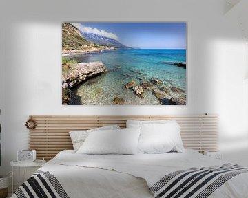 Kust met blauwe zee, rotsen en bergen in Griekenland van Ben Schonewille