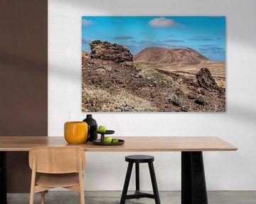 Landschap Lanzarote met lava rotsblokken op de voorgrond. van Harrie Muis