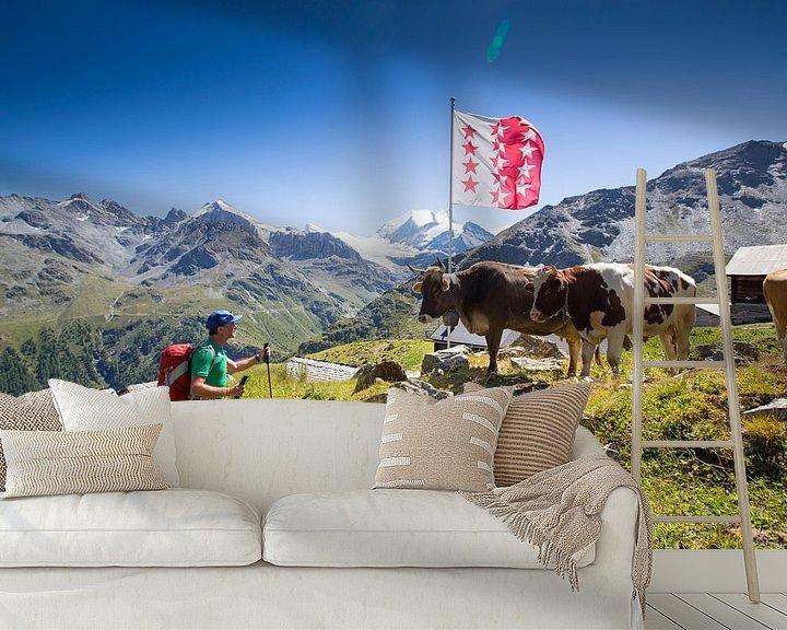 Sfeerimpressie behang: Een bergwandelaar oog in oog met koeien in Wallis van Menno Boermans