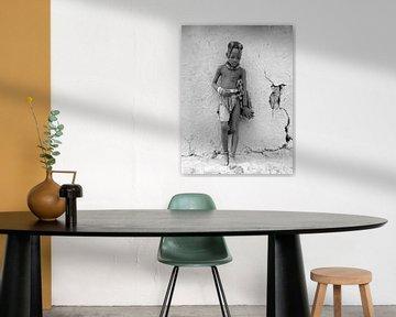 Himba kind tegen de muur van de hut.
