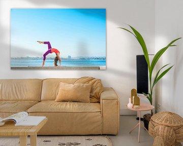 Jonge vrouw beoefent yoga op een smalle muur aan de kust van BeeldigBeeld Food & Lifestyle