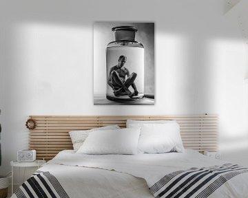 Surrealistisches Schwarz-Weiß-Phantasiebild eines flüssig konservierten Mannes in einem Glas. von Hans Post