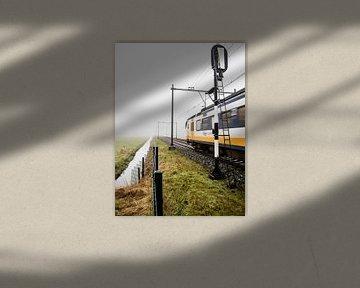 Un train typiquement hollandais sort du brouillard et passe un signal de chemin de fer sur Hans Post