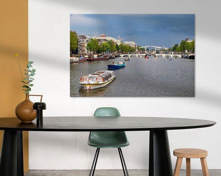 Sfeerimpressie: De Amstel in Amsterdam met een rondvaartboot en donkere lucht van Sjoerd van der Wal