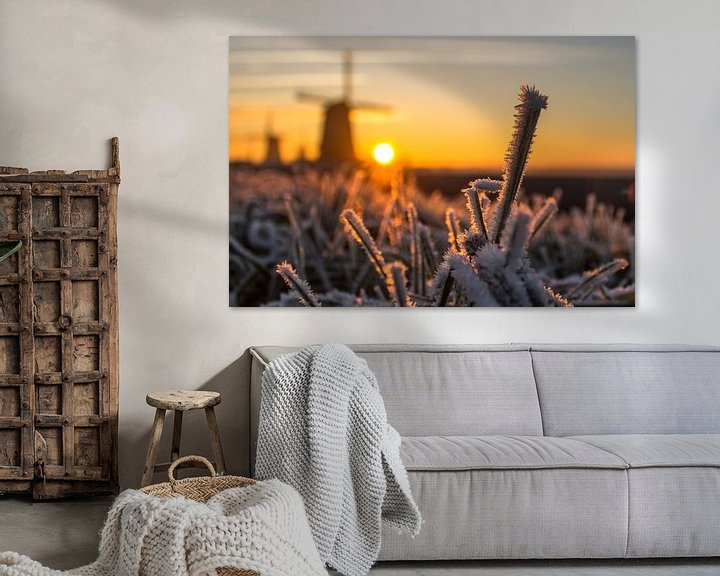 Sfeerimpressie: Rijp op de grassprieten in het Nederlandse landschap waar de molens tijdens zonsondergang op de acht van Dennis Dieleman