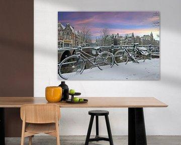 Besneeuwd Amsterdam in de winter bij zonsondergang von Nisangha Masselink