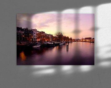Stadsgezicht van Amsterdam aan de Amstel in Nederland bij avond von Nisangha Masselink