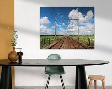 Spoorwegovergang met oneindig spoor naar de horizon met felle blauwe lucht