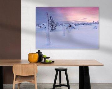 Ondergesneeuwd  dorp tijdens pastelkleurige zonsondergang van Rob Kints