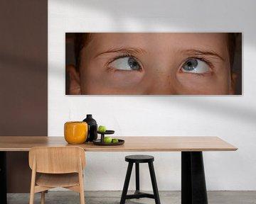 Junge, der mit blauen Augen schielen schaut
