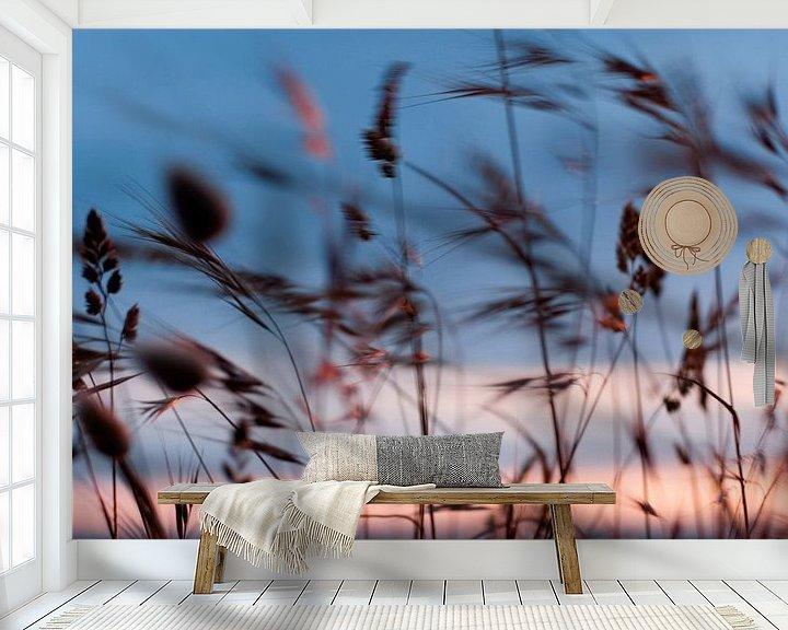 Sfeerimpressie behang: Wuivende grashalmen aan de kust, met zonsondergang  van Margo Schoote