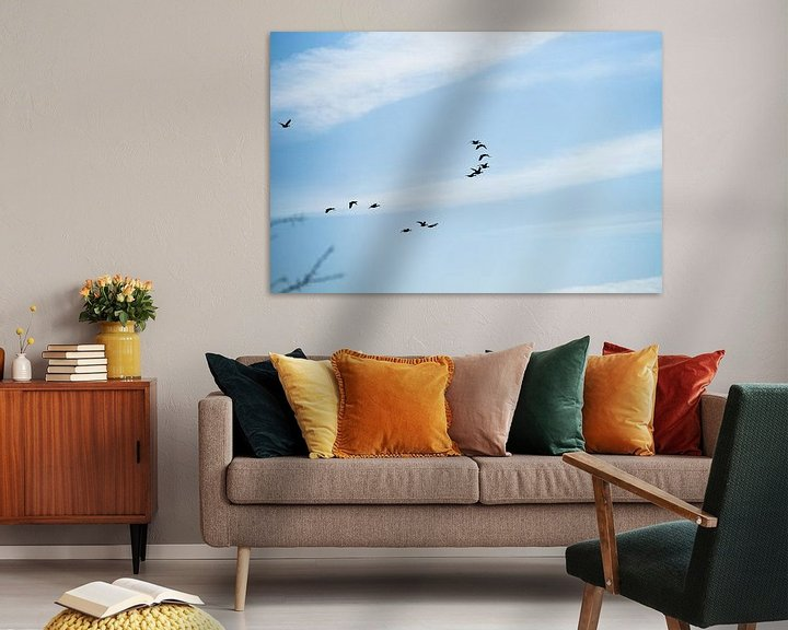 Sfeerimpressie: Groep vogels in formatie tegen een blauwe lucht van Fotografiecor .nl