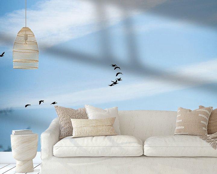 Sfeerimpressie behang: Groep vogels in formatie tegen een blauwe lucht van Fotografiecor .nl