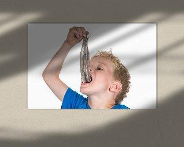 jongen eet een haring van Marcel Mooij