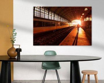 Silhouet van een man op treinstation tijdens zonsondergang van Rob Kints