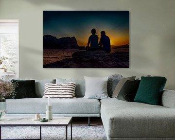 romantisch stel kijkt vanuit een hoge rots , naar de ondergaande zon  in de woestijn  van Wadi-rum   van Rita Phessas