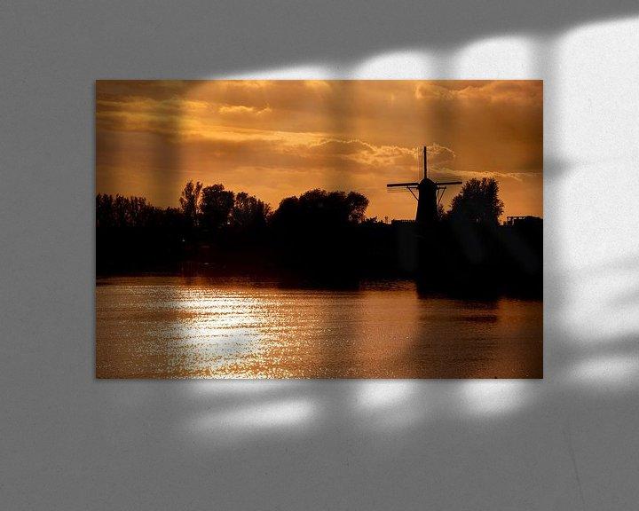 Sfeerimpressie: Avondlucht met zon op het water en een Windmolen. van Brian Morgan