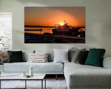 Oranje zonsopgang boven een boot met zonnestralen van Gea Gaetani d'Aragona